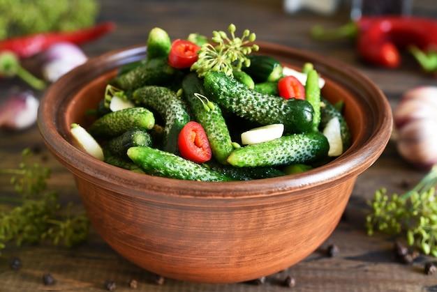 Petits concombres à l'aneth, poivre et ail marinés sur la table de la cuisine. pikuli. cornichons.
