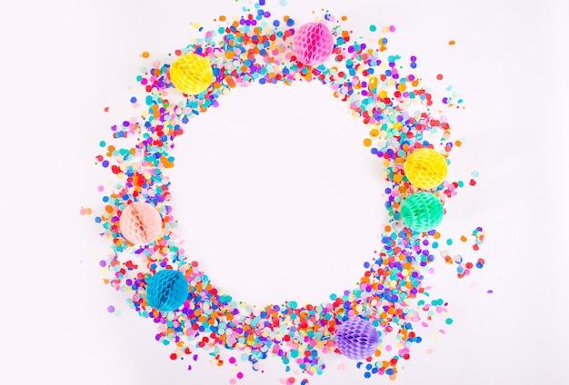 Petits confettis multicolores sur fond blanc. vue de dessus.