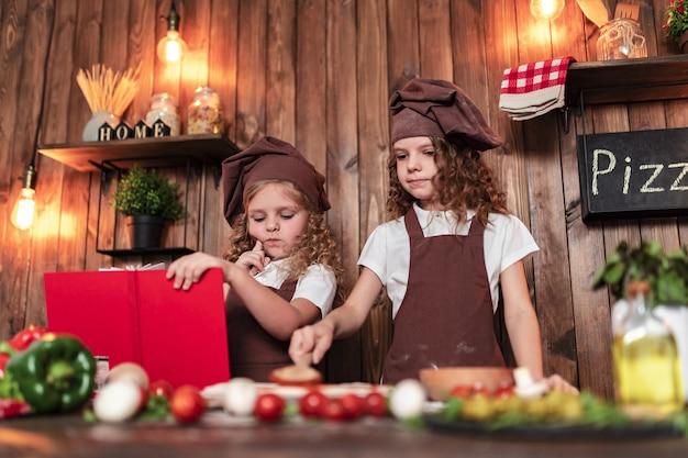 Petits cuisiniers lisant un livre de recettes