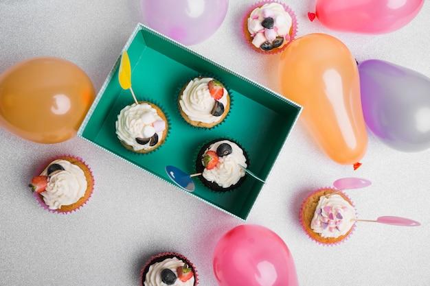 Petits cupcakes avec des ballons à air sur table