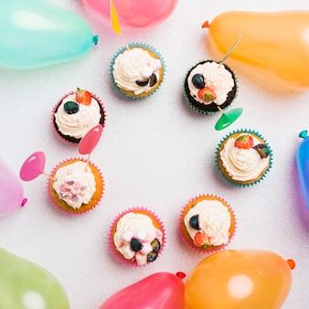 Petits cupcakes sucrés avec des ballons à air chaud sur table lumineuse