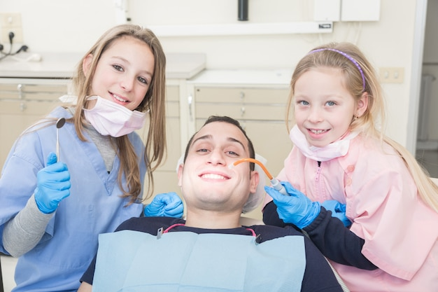 Petits dentistes examinant la bouche d'un patient adulte