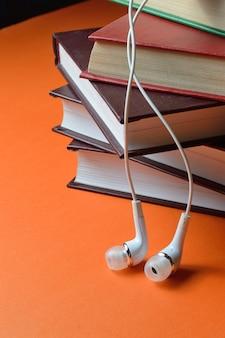 De petits écouteurs blancs du téléphone se trouvent sur une pile de livres.