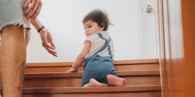 Les petits enfants en bas âge avec la première marche avec des escaliers à la maison, les petits bébés sont heureux de jouer et d'apprendre à ramper avec la famille, les bébés mignons s'amusant et s'occupant des enfants