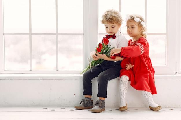 Petits enfants élégants avec bouquet de tulipe