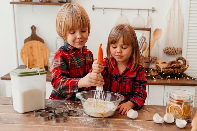 Petits enfants faisant des biscuits de noël