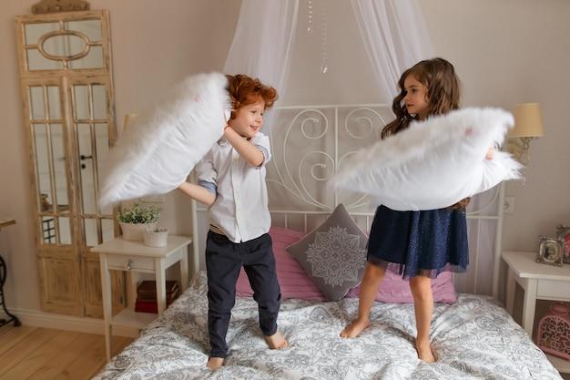 Petits enfants, garçon et fille jouant avec des oreillers sur le lit.