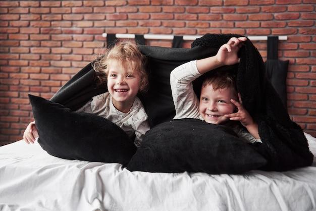 Petits enfants, garçon et fille portant et jouant avec des oreillers sur le couvre-lit avec une couverture
