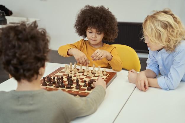 Petits enfants géniaux discutant du jeu assis à la table et jouant aux échecs à l'intérieur