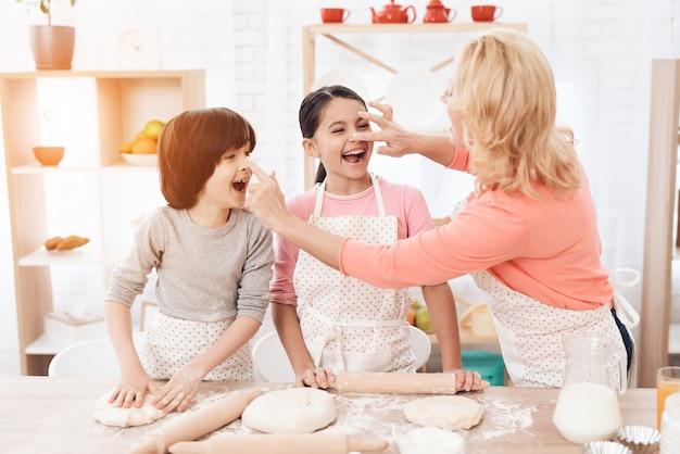 Petits-enfants et grand-mère s'amusant dans la cuisine
