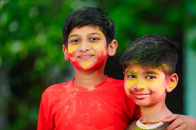 Petits enfants indiens mignons jouant à holi. holi est le festival des couleurs en inde