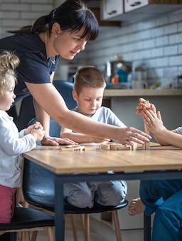 Les petits enfants jouent à un jeu de société avec des cubes en bois à la maison dans la cuisine avec maman.