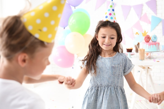 Petits enfants mignons célébrant l'anniversaire à la maison