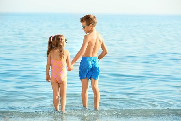 Petits enfants mignons sur la plage de la mer