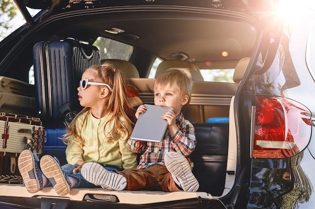 Petits enfants mignons s'amusant dans le coffre d'une voiture avec des valises route familiale