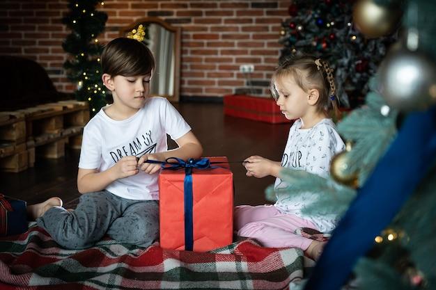 Les petits enfants ouvrent des cadeaux dans une maison confortable pour célébrer noël