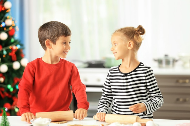 Petits enfants préparant des biscuits de noël dans la cuisine