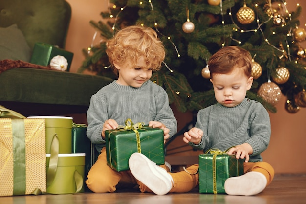 Petits enfants près de sapin de noël dans un pull gris