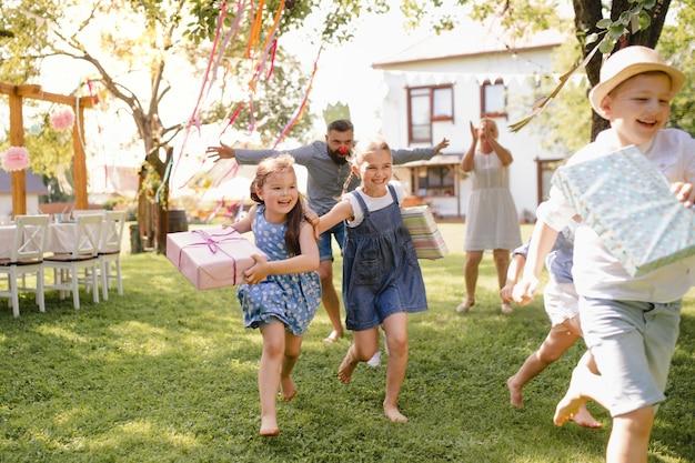 Petits enfants qui courent avec un cadeau à l'extérieur dans le jardin lors d'une fête d'anniversaire, jouent.
