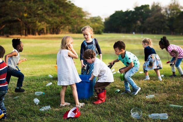 Petits enfants séparant les bouteilles de recyclage dans la corbeille