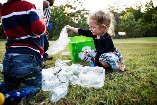 Petits enfants séparant le plastique recyclé dans la corbeille