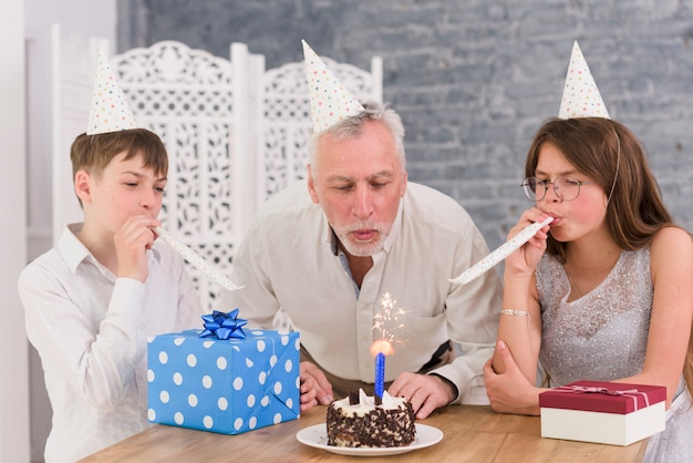 Petits-enfants soufflant des cornes de fête avec leur grand-père soufflant de sparkler sur un gâteau d'anniversaire