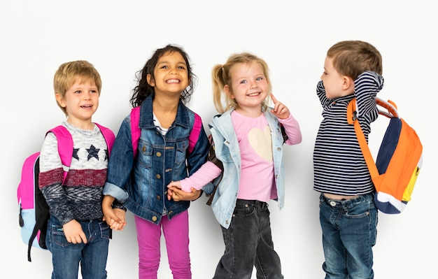 Petits enfants tenant par la main portant des sacs à dos