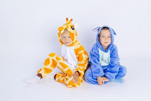 Petits frères en costumes drôles assis sur un fond blanc