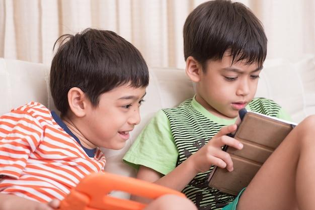 Petits frères et sœurs garçons jouant au jeu sur tablette