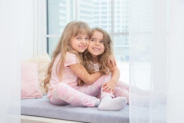 Petits frères et sœurs mignons assis sur le rebord de la fenêtre à la maison s'embrassant