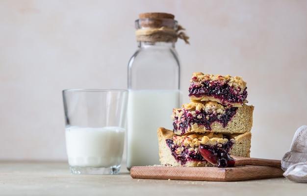 Petits fruits faits maison confiture de carrés de pâte brisée et verre de lait fond de béton léger mise au point sélective