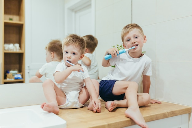 Petits garçons enfants se brosser les dents dans la salle de bain, deux frères