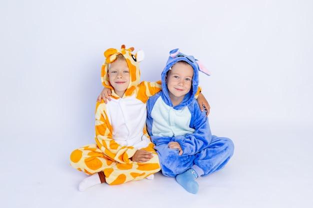 Petits garçons frères en costumes lumineux amusants s'asseoir sur le sol