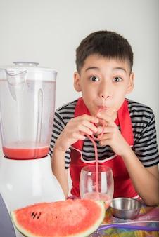 Petits garçons mélangent le jus de melone d'eau en utilisant un mélangeur à la maison