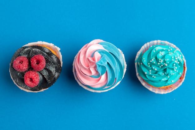 Petits gâteaux d'anniversaire sur le bleu se bouchent