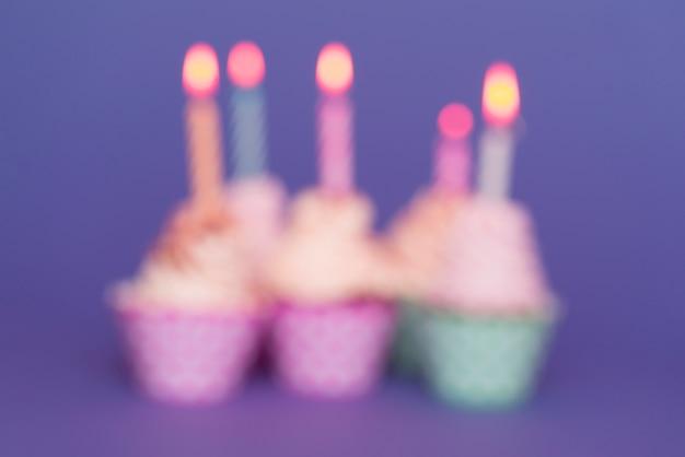 Petits gâteaux d'anniversaire flou avec des bougies allumées