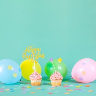 Petits gâteaux d'anniversaire roses avec des ballons