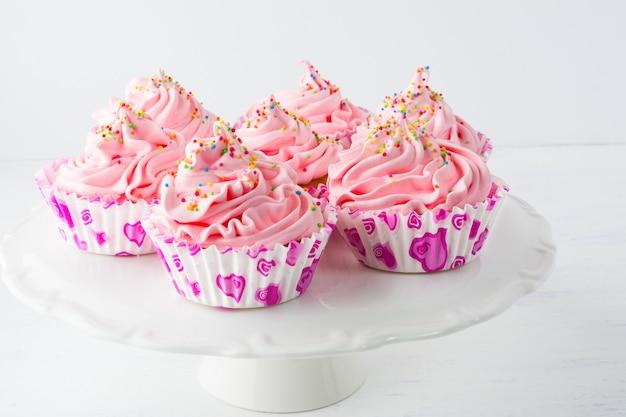 Petits gâteaux d'anniversaire roses décorés sur le présentoir à gâteaux