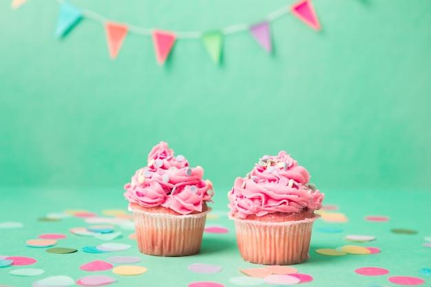 Petits gâteaux d'anniversaire roses avec guirlande