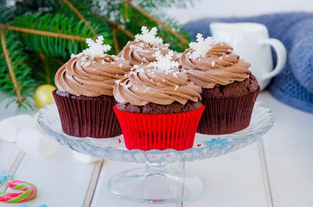 Petits gâteaux au chocolat avec de la crème au fromage au chocolat avec une tasse de café et des guimauves pour noël et le nouvel an sur un blanc en bois.