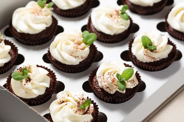 Petits gâteaux au chocolat avec crème au fromage et feuilles de menthe dans une boîte de livraison