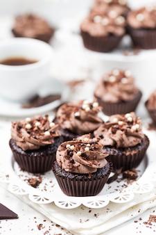 Petits gâteaux au chocolat décorés de crème au fromage café sur une plaque blanche