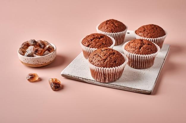 Petits gâteaux au chocolat faits maison dans des formes de papier sulfurisé sur une planche à découper sur fond rose poudré