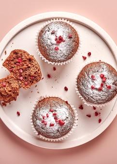 Petits gâteaux au chocolat faits maison sous forme de papier sulfurisé et morceau de celui-ci sur plaque légère sur poudre rose