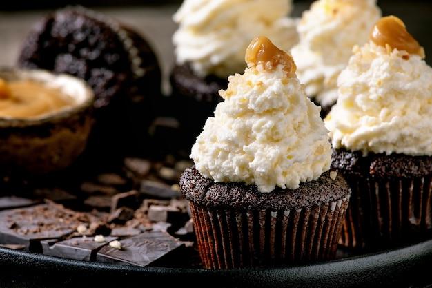 Petits gâteaux au chocolat maison muffins avec crème au beurre fouettée blanche et caramel salé, servis avec du chocolat noir haché sur une plaque en céramique noire. fermer
