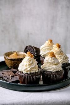 Petits gâteaux au chocolat maison muffins avec crème au beurre fouettée blanche et caramel salé, servis avec du chocolat noir haché sur plaque en céramique noire sur nappe blanche