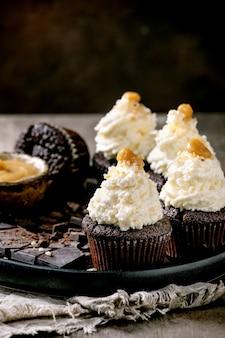 Petits gâteaux au chocolat maison muffins avec crème au beurre fouettée blanche et caramel salé, servis avec du chocolat noir haché sur une plaque en céramique noire sur une table de texture en béton.