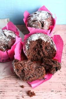 Petits gâteaux au chocolat en papier rose sur table en bois, gros plan