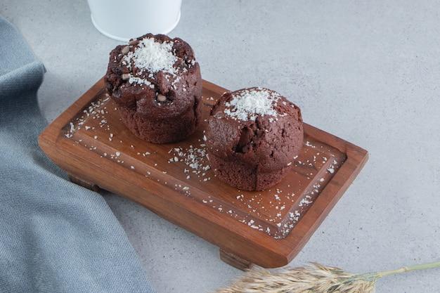 Petits gâteaux au chocolat sur une planche sur fond de marbre.
