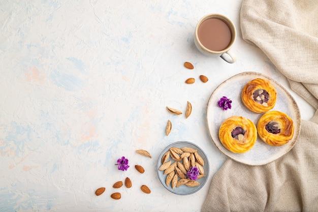 Petits gâteaux au fromage avec de la confiture et des amandes avec une tasse de café sur un béton blanc